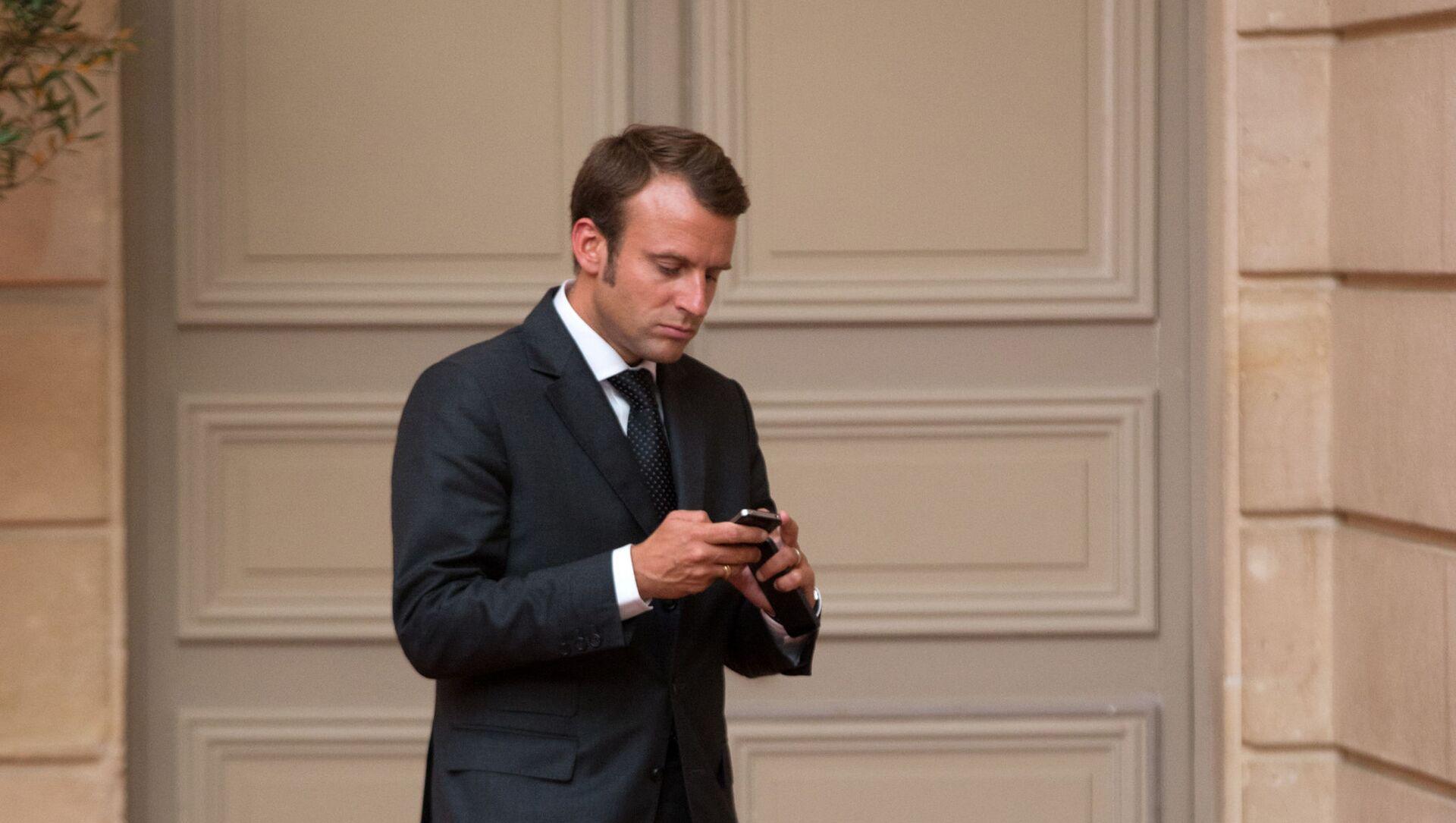 Emmanuel Macron, looks at his phone - Sputnik International, 1920, 25.07.2021