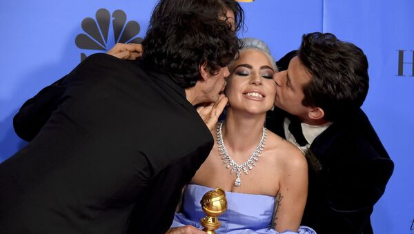 Anthony Rossomando, from left, Andrew Wyatt, and Mark Ronson, right, kiss Lady Gaga, second right, as they pose in the press room with the award for best original song, motion picture for Shallow from the film A Star Is Born at the 76th annual Golden Globe Awards - Sputnik International