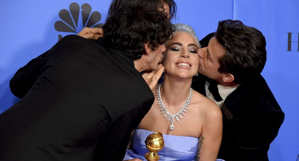 Anthony Rossomando, from left, Andrew Wyatt, and Mark Ronson, right, kiss Lady Gaga, second right, as they pose in the press room with the award for best original song, motion picture for Shallow from the film A Star Is Born at the 76th annual Golden Globe Awards