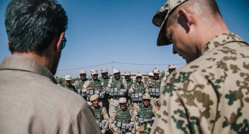 Kurdish Peshmerga soldiers listen to instructions by a German army trainer, at Bnaslawa Military Base in Irbil, northern Iraq
