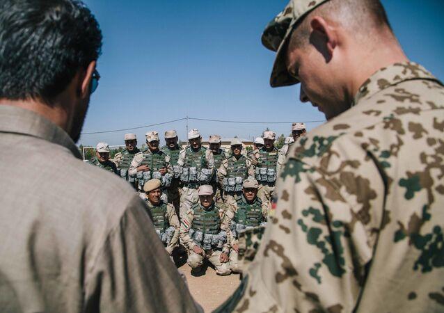 Kurdish Peshmerga soldiers listen to instructions by a German army trainer, at Bnaslawa Military Base in Irbil, northern Iraq