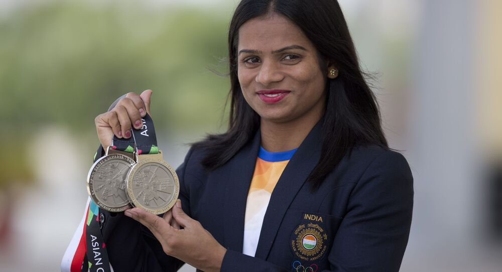 Indian sprinter Dutee Chand displays her silver medals during a press conference in Hyderabad, India, Saturday, Sept. 1, 2018