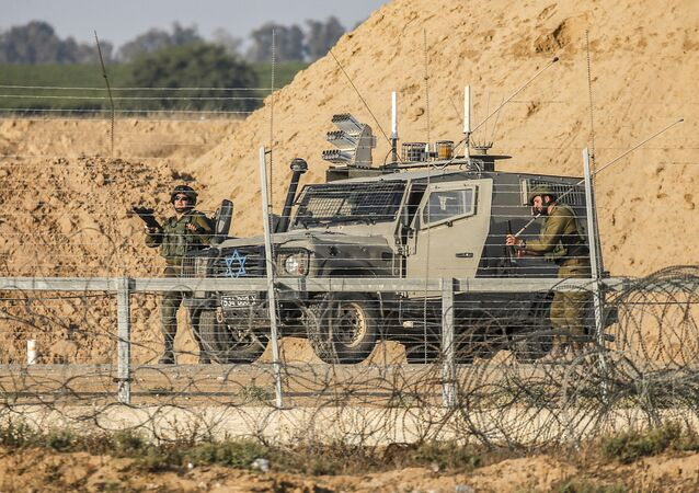 Israeli soldiers are seen next to a military vehicle across the barbed-wire border fence with the Gaza Strip
