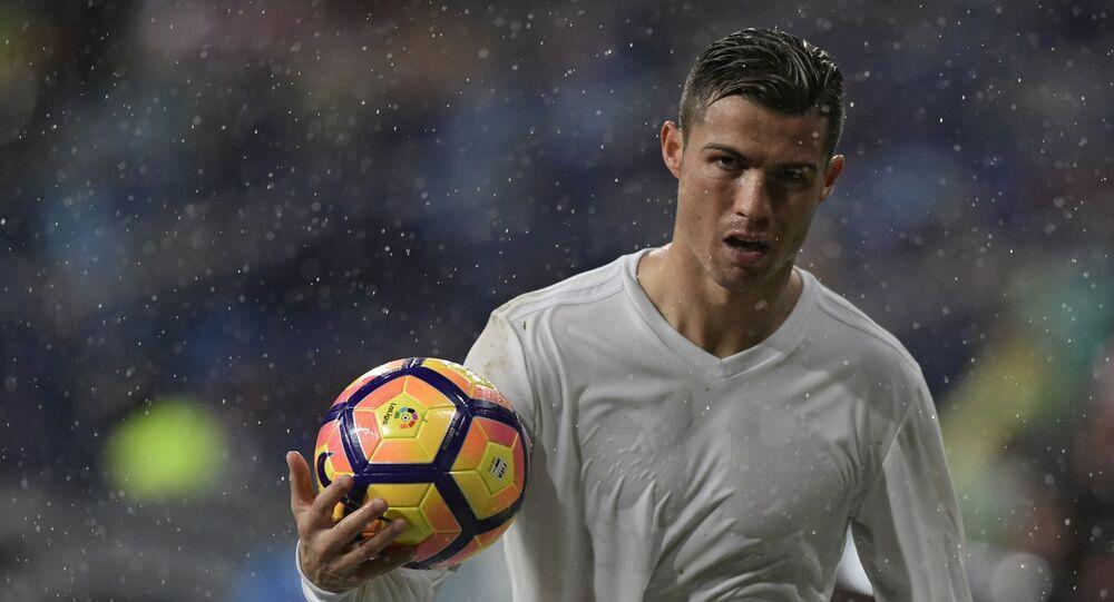 Real Madrid's Portuguese forward Cristiano Ronaldo holds a ball during the Spanish league football match Real Madrid CF vs Sporting de Gijon SAD at the Santiago Bernabeu stadium in Madrid on November 26, 2016