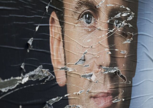 A  picture taken in Paris on May 5, 2017 shows vandalised campaign posters of French presidential election candidate for the En Marche ! movement, Emmanuel Macron