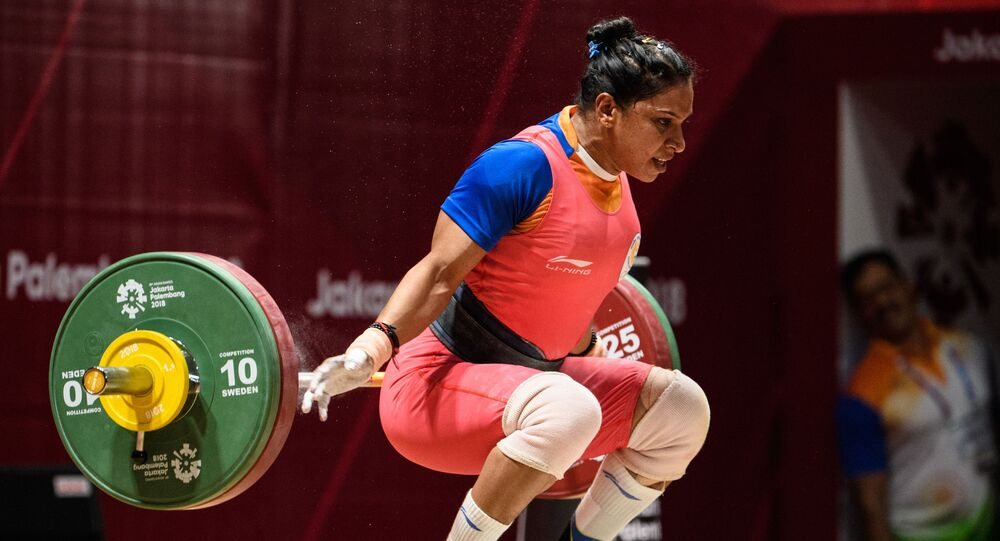 India's Rakhi Halder takes part in the women's 63kg Group A weightlifting event at the 2018 Asian Games in Jakarta on August 24, 2018. (Photo by ANTHONY WALLACE / AFP)