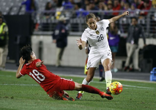 FILE - In this Dec. 13, 2015, file photo, China's Han Peng (18) slides in to knock the ball away from United States' Jaelene Hinkle during the second half of an international friendly soccer match, in Glendale, Ariz