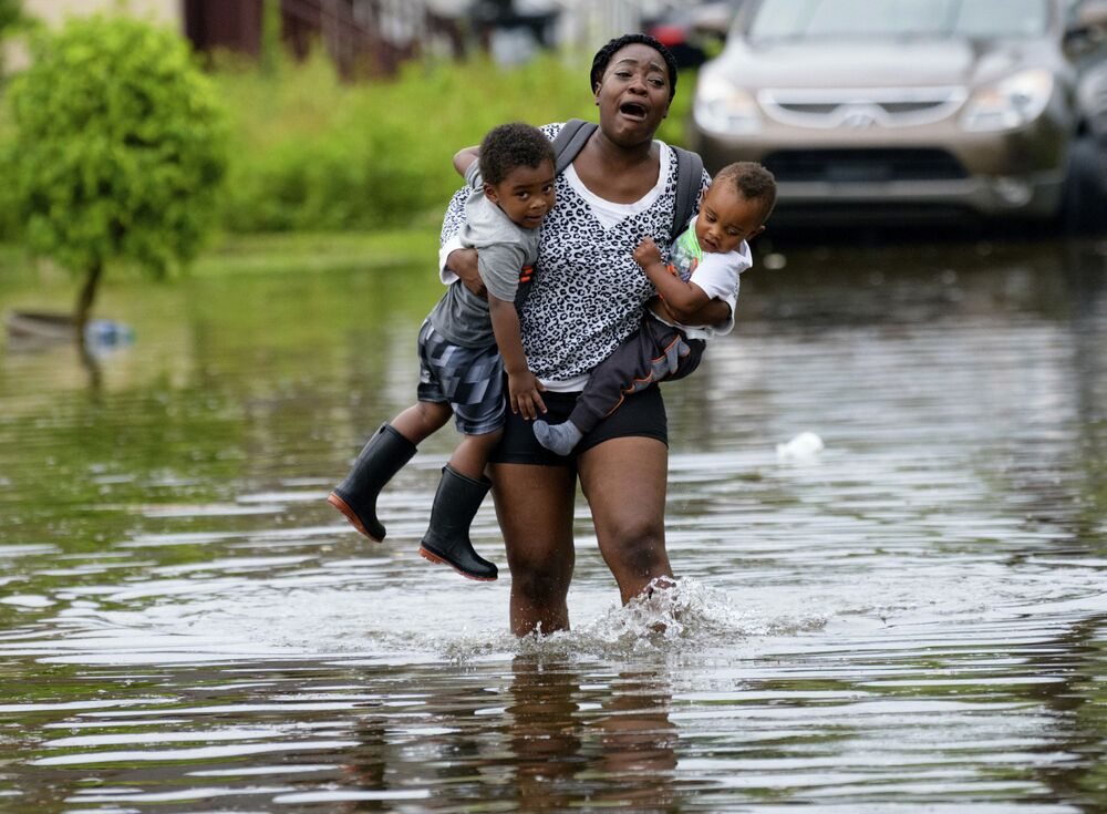A woman carries children on Belfast Street in New Orleans during flooding from a storm in the Gulf Mexico that dumped lots of rain Wednesday, July 10, 2019.