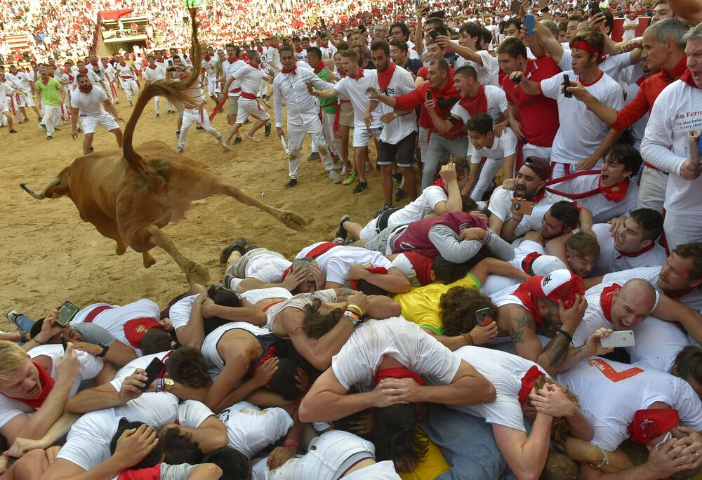 A heifer jumps over revellers in the bullring after the second bullrun the San Fermin festival in Pamplona, northern Spain on July 8, 2019.
