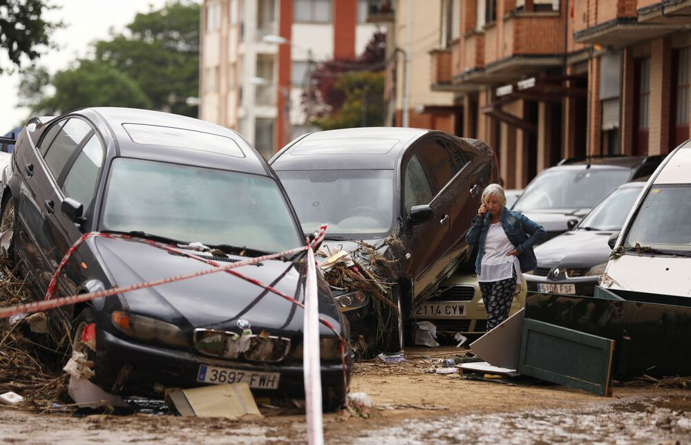 A woman speaks on the phone next to damaged cars after heavy rainfall in Tafalla, Spain, July 9, 2019.