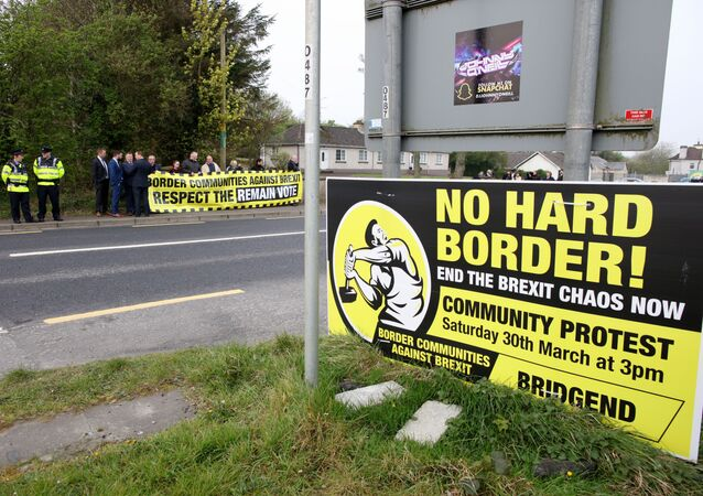 Protesters against Brexit and the possible imposition of any hard border between Northern Ireland and Ireland  gather with a banner at the border (marked where the tarmac changes and the lines change between white and yellow) between Derry (Londonderry) in Northern Ireland and County Donegal in the Republic of Ireland near the Irish village of Bridge End on April 18, 2019