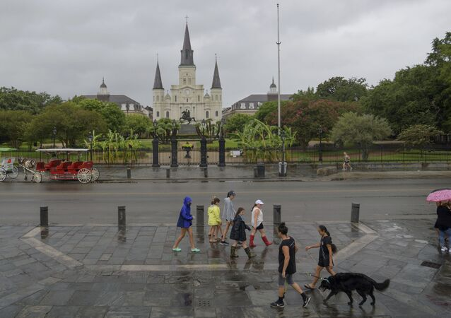People walk past Jackson Square and St. Louis Cathedral in the French Quarter before landfall of Tropical Storm Barry from the Gulf of Mexico in New Orleans, La., Friday, July 12, 2019.