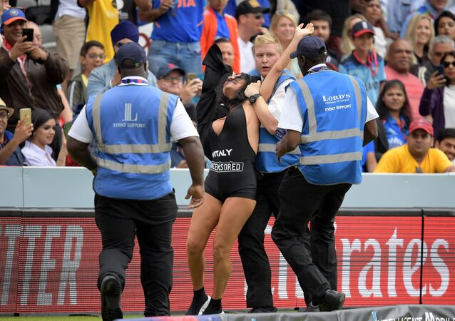 Security personnel detain a pitch invader during the 2019 Cricket World Cup final between England and New Zealand at Lord's Cricket Ground in London on July 14, 2019.