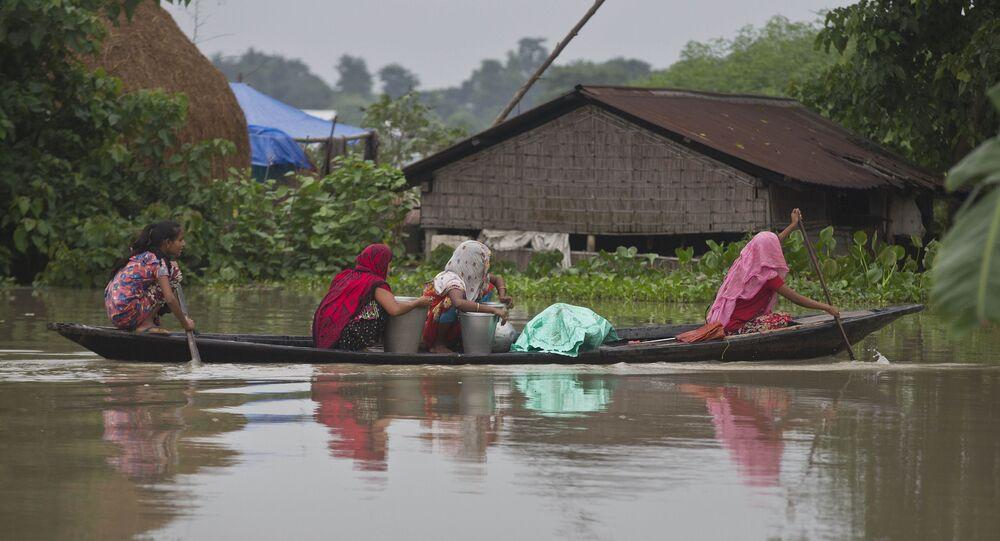 Indian flood affected women transport drinking water on a boat in Burha Burhi village