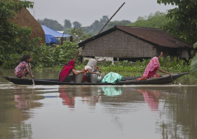 Indian flood affected women transport drinking water on a boat in Burha Burhi village