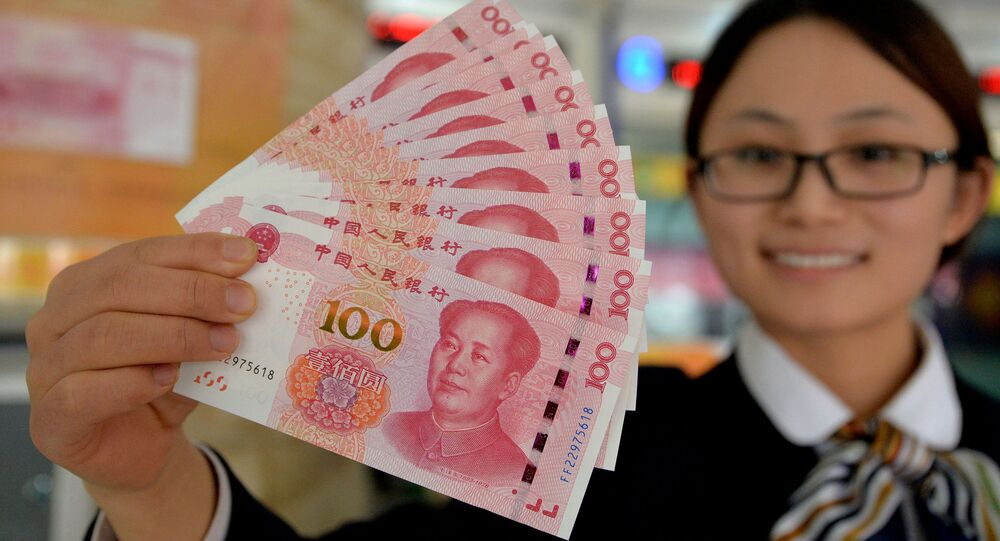 A bank employee shows new 100-yuan banknotes in Handan, north China's Hebei province on November 12, 2015