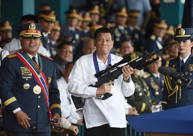 Philippine President Rodrigo Duterte holds a Galil sniper rifle next to outgoing Philippine National Police Chief Ronald Bato Dela Rosa during the National Police chief handover ceremony in Camp Crame, Quezon City, metro Manila, Philippines, April 19, 2018