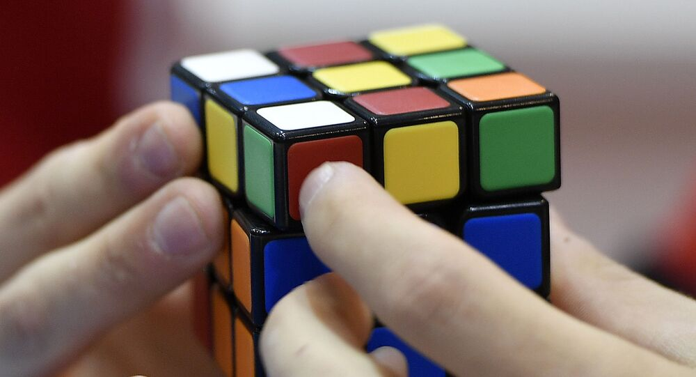 A gamer plays with Rubik's Magic Cube at the international game fair 'SPIEL' in Essen, Germany, Thursday, 26 October 2017. Around 1100 exhibitors from around 50 nations attend the annual four-day game fair. (AP Photo/Martin Meissner)