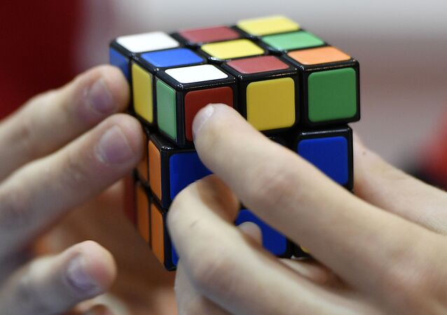 A gamer plays with Rubik's Magic Cube at the international game fair 'SPIEL' in Essen, Germany, Thursday, Oct. 26, 2017. Around 1100 exhibitors from around 50 nations attend the annual four-day game fair. (AP Photo/Martin Meissner)
