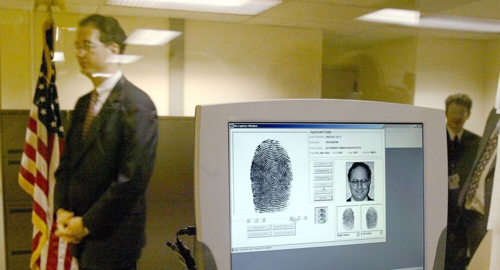 A U.S. embassy official walks past a monitor displaying biometric data during a demonstration of a new procedure, fingerprint scans, to the media at the U.S. Embassy in Moscow