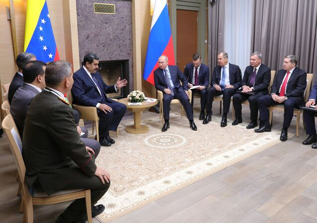 Venezuelan President Nicolas Maduro, background left, and Russian President Vladimir Putin, background center, attend the talks at the Novo-Ogaryovo residence outside Moscow, Russia, Wednesday, Dec. 5, 2018.