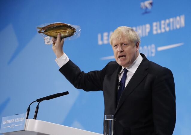 Conservative MP and leadership contender Boris Johnson holds up kipper fish in plastic packaging as he speaks at the final Conservative Party leadership election hustings in London, on July 17, 2019