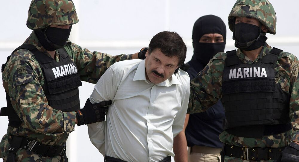 In this 22 February 2014 file photo, Joaquin El Chapo Guzman, centre, is escorted to a helicopter in handcuffs by Mexican navy marines at a hanger in Mexico City, after he was captured overnight in the beach resort town of Mazatlan.