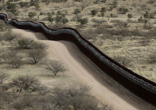 In this March 2, 2019 file photo, a razor-wire-covered border wall separates the United States, at left, from Mexico east of Nogales, Ariz