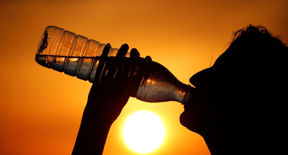 A woman drinks water during sunset, as a heatwave