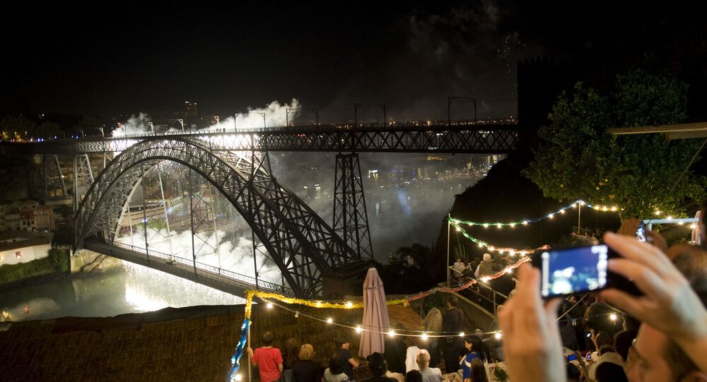 Revelers watch fireworks at Dom Luis Bridge spanning over Douro River