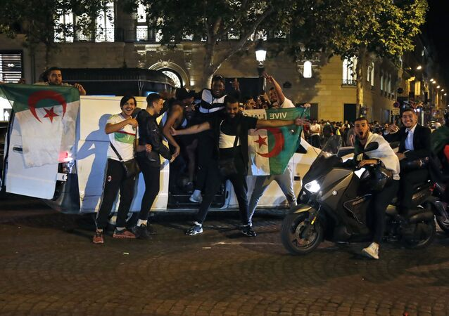 Algeria's supporters celebrate with the Algerian national flag in the Champs Elysee Avenue in Paris, after Algeria won 1-0 the 2019 Africa Cup of Nations (CAN) final football match between Algeria and Senegal, on July 19, 2019