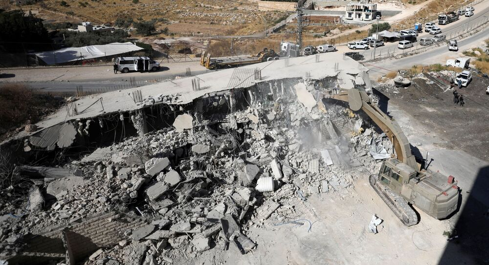 An Israeli military bulldozer demolishes a building near a military barrier in Sur Baher, a Palestinian village on the edge of East Jerusalem in an area that Israel captured and occupied in the 1967 Middle East War July 22, 2019