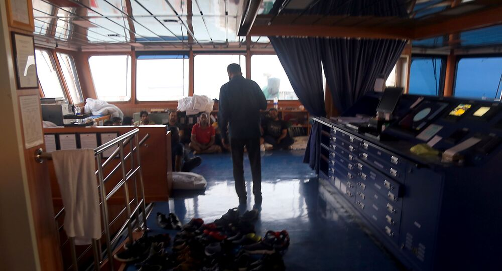 In this handout picture provided by Fars news, an Iranian official talks to crew members inside the seized UK-flagged tanker Stena Impero off the coast of Bandar Abbas in southern Iran, on 21 July 2019