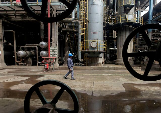 A worker walks past oil pipes at a refinery in Wuhan, Hubei province, China