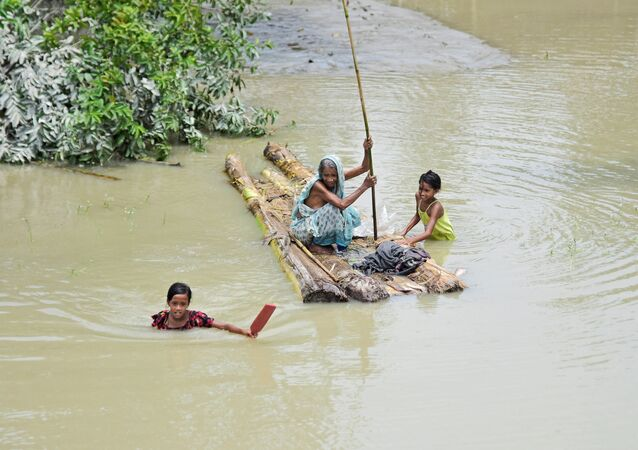 A woman rows a makeshift raft as girls wade through flood waters at the Laharighat village in Morigaon district, in the northeastern state of Assam, India, July 21, 2019