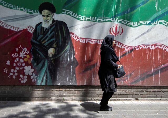 An Iranian woman walks in front of a mural of Iran's late leader Ayatollah Ruhollah Khomeini in Tehran, Iran July 7, 2019