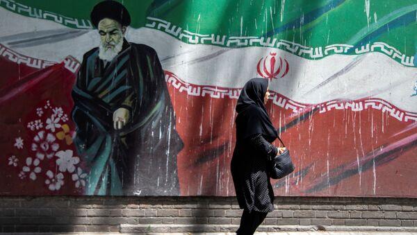 An Iranian woman walks in front of a mural of Iran's late leader Ayatollah Ruhollah Khomeini in Tehran, Iran July 7, 2019 - Sputnik International