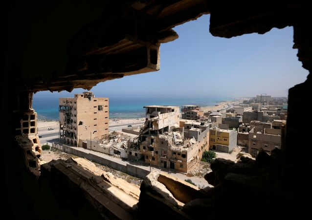 Destroyed buildings are seen through a hole in Benghazi lighthouse after it was severely damaged by years of armed conflict, in Benghazi, Libya July 10, 2019