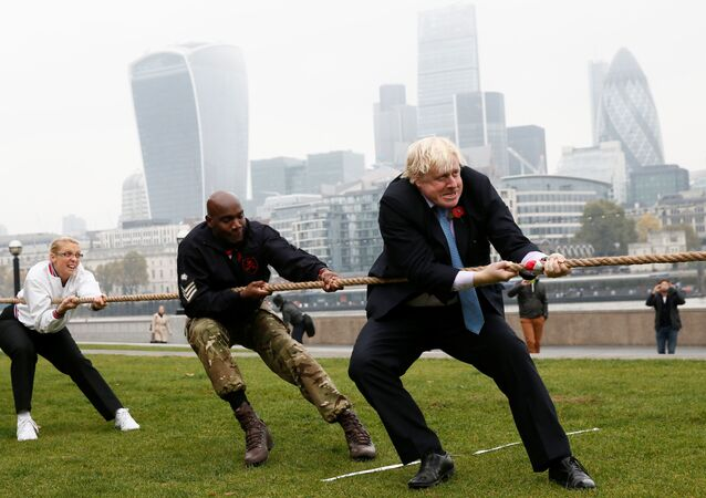 London Mayor Boris Johnson takes part in a tug of war with members of the armed services to launch the London Poppy Day, outside City Hall, in London, October 27, 2015