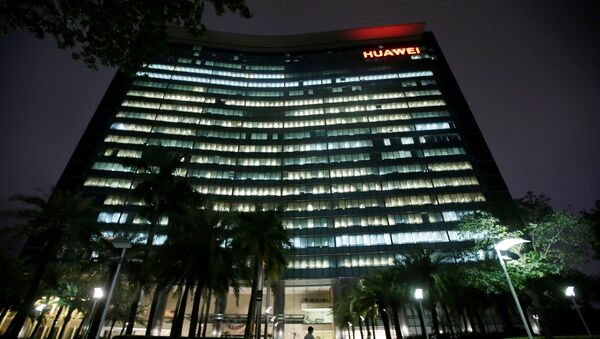 Employees walk past a research and development building with lights on at Huawei headquarters in Shenzhen - Sputnik International