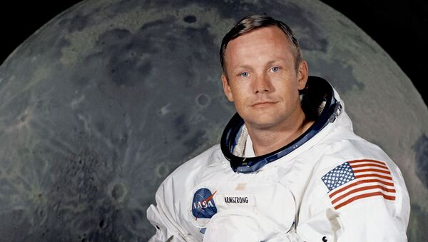 Portrait of Astronaut Neil A. Armstrong, commander of the Apollo 11 Lunar Landing mission in his space suit, with his helmet on the table in front of him. Behind him is a large photograph of the lunar surface. - Sputnik International