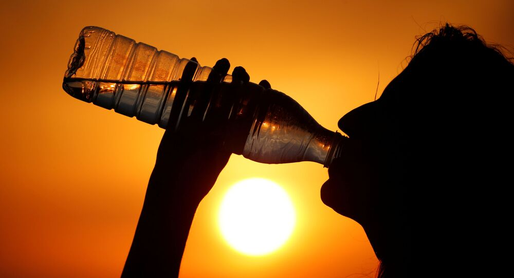 A woman drinks water during sunset, as a heatwave hits France, in Cagnicourt near Cambrai, France, June 25, 2019
