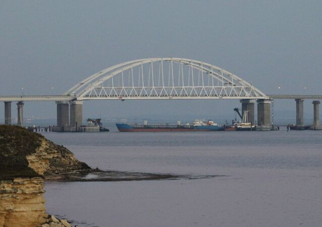 A cargo ship blocks a passage under the arch of the Crimean bridge over Kerch Strait in Russia, November 25, 2018