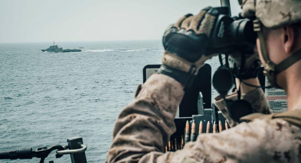 A U.S. Marine observes an Iranian fast attack craft from USS John P. Murtha during a Strait of Hormuz transit, Arabian Sea off Oman