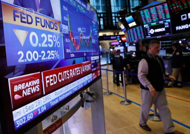 A screen displays the U.S. Federal Reserve interest rates announcement as traders work on the floor of the New York Stock Exchange (NYSE) in New York, U.S., July 31, 2019.