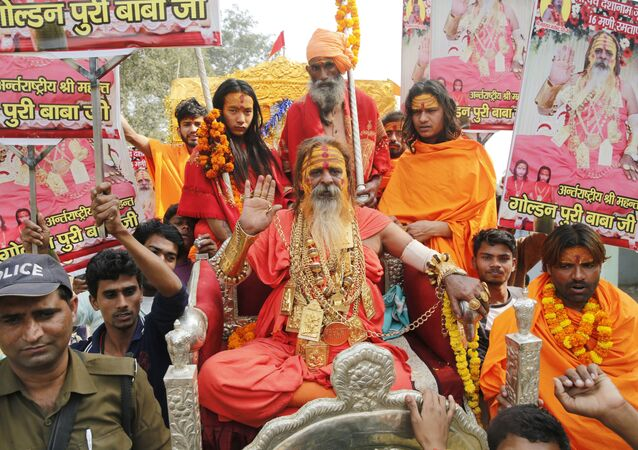 Indian godman Golden Baba, known for the gold ornaments he wears gestures as Hindu holy men arrive in a procession ahead of the Kumbh Mela in Allahabad, India, Wednesday, Nov. 28, 2018