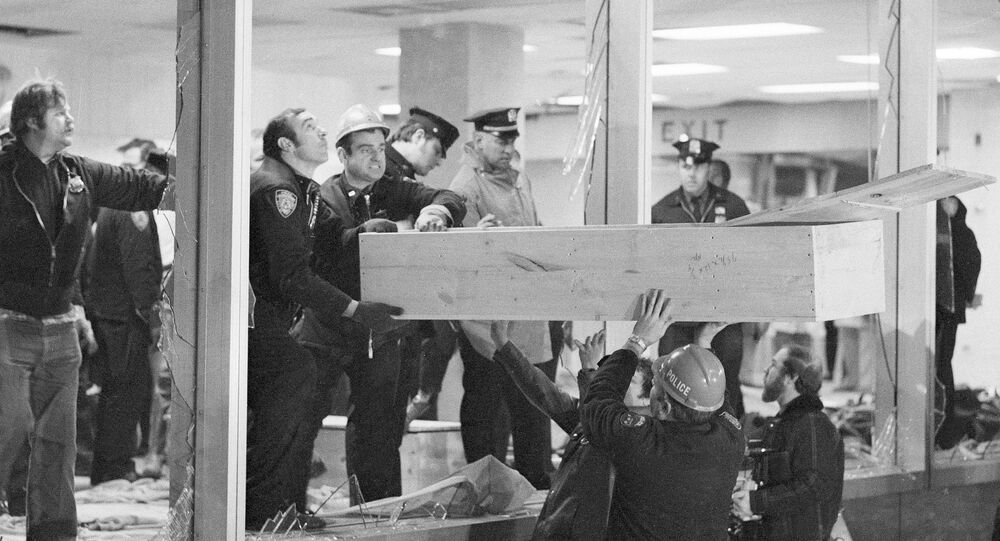 Rescue workers lift a coffin through a shattered window at New York's La Guardia airport after a bombing in 1975
