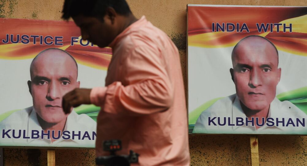 An Indian resident walks past placards with the picture of Kulbhushan Jadhav, an Indian national convicted of spying in Pakistan, in the neighborhood where he grew up, in Mumbai on July 17, 2019