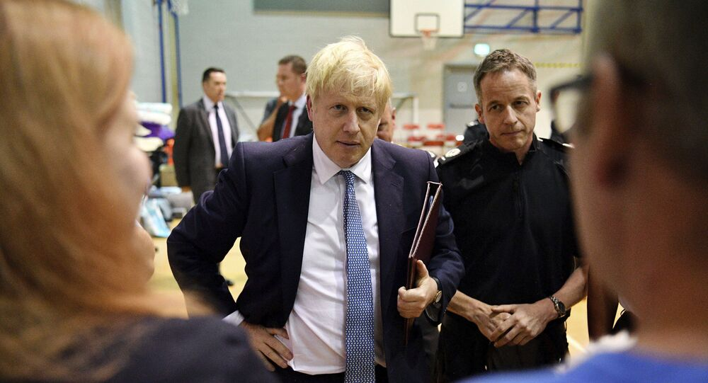 Britain's Prime Minister Boris Johnson meets with rescue crews and local residents during a visit to Chapel-en-le-Frith High School near the village of Whaley Bridge in Derbyshire, England