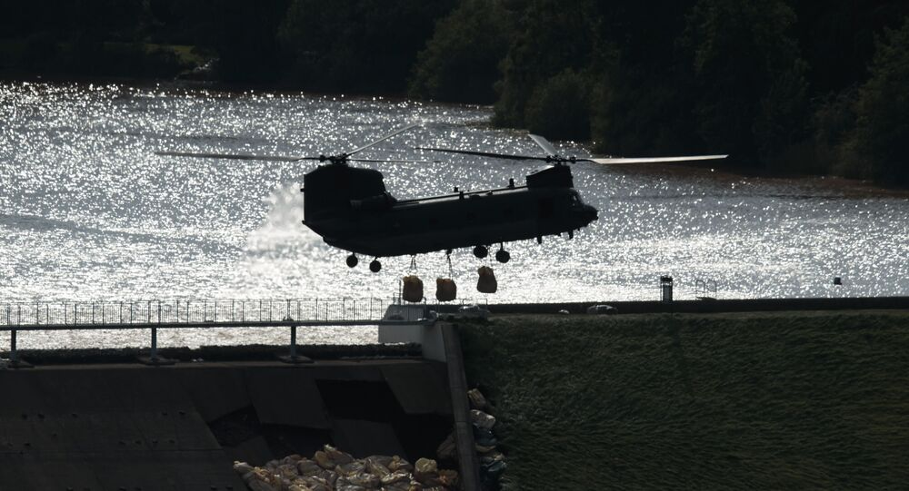 An RAF Chinook helicopter drops aggregate to help shore up a reservoir at risk of collapse, threatening to engulf the town of Whaley Bridge in the Peak District, England, Friday